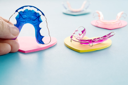 Dental retainer orthodontic appliance on the blue background.