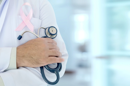 doctor with pink ribbon concept cancer and stethoscope.