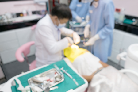 Blurred image photo of dentist and his assistant are working in clinic.