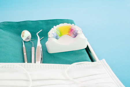 Dental retainer orthodontic appliance and dental tools on the blue background. 版權商用圖片
