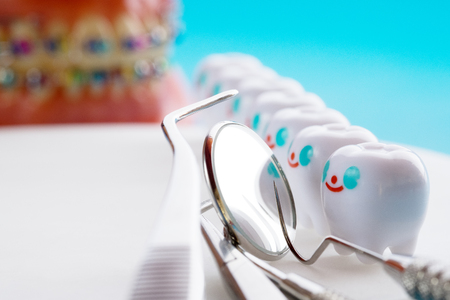 Close up.Dentist tools and smile teeth model on white background.