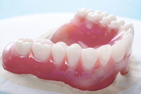 Close up , Complete denture or full denture on blue background. Reklamní fotografie