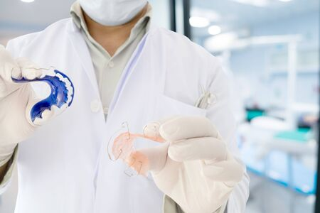 Dentist show dental retainer orthodontic appliance in his hand / in office or clinic. Stock Photo