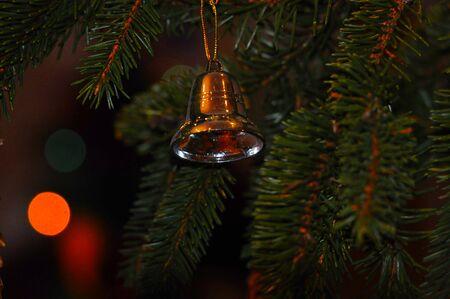 Yelow handbell on the Christmas tree. Stock Photo