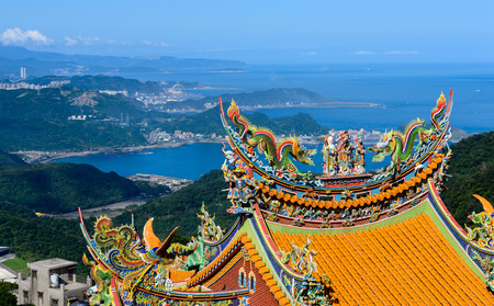 Yellow  Orange Roof temple high up in the mountain with distant sea water and landscapes