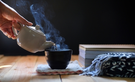Gießen von heißem Tee in Teekanne und Tasse auf Holztisch, schwarzer Hintergrund. Teezeit im Winter. Standard-Bild