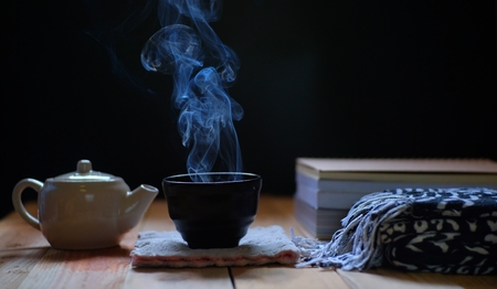 hot tea in teapot and cup on wood table, black background. Winter tea time.