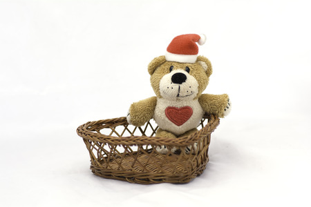 Doll in a wicker basket on a white background . Stock Photo