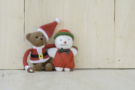 greatly: Stuffed Santa Claus and snowman on the wooden floor.
