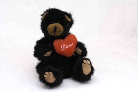 narratives: Stuffed bear on a heart-shaped, white background.