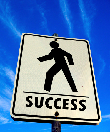 white pedestrian walking with success word sign in the blue sky background