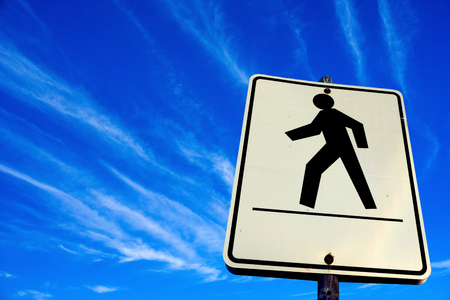 white pedestrian walking sign in the blue sky background