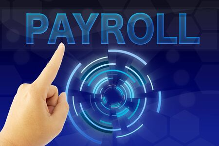 hand pointing PAYROLL word on blue screen Stock Photo