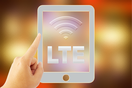 lte: hand touch tablet LTE over blurred background Stock Photo