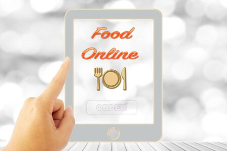 online: touching screen order food online with blur bokeh background