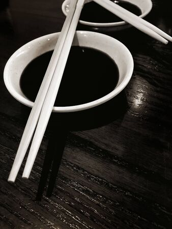 sauce bowl: Japanese sushi chopsticks with soy sauce bowl on black wooden background