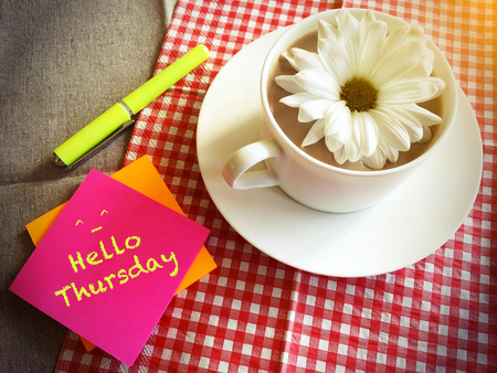 thursday: coffee cup on table with white daisy and words Hello Thursday vintage style