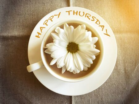thursday: coffee cup on table with white daisy - Happy Thursday word vintage style