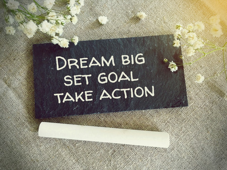 set goal: Blackboard for your text and flowers with words dream big set goal take action Stock Photo