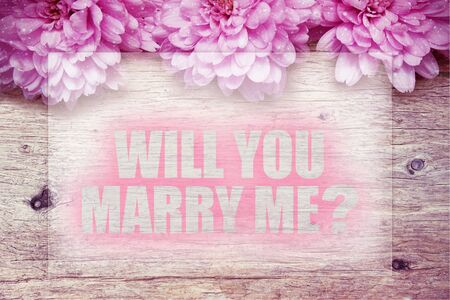 pink flowers on wooden with word Will you marry me?