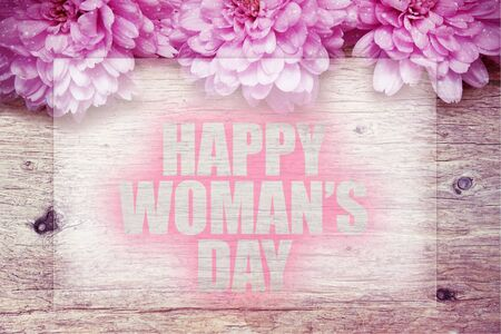 pink flowers on wooden with word Happy Womans Day Stock Photo