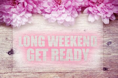 get ready: pink flowers on wooden with word Long weekend get ready