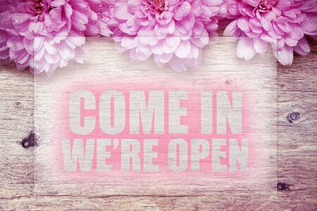 come in: pink flowers on wooden with word Come in were open
