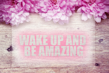 pink flowers on wooden with word Wake up and be amazing Stock fotó