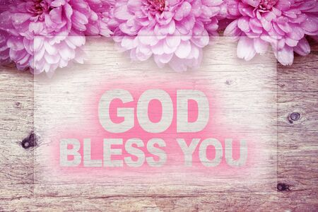 god bless: pink flowers on wooden with word GOD BLESS YOU Stock Photo