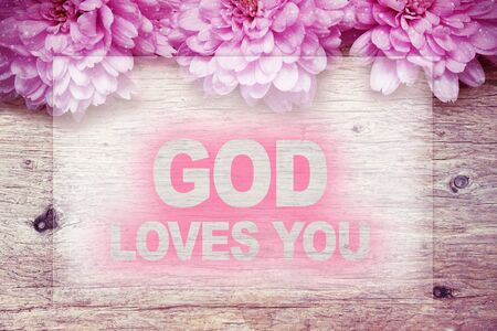 pink flowers on wooden with word GOD LOVES YOU