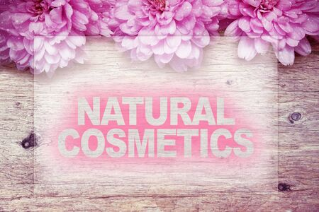 natural cosmetics: pink flowers on wooden with word NATURAL COSMETICS