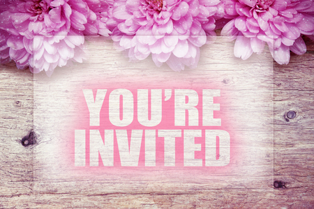 invited: pink flowers on wooden with word Yourre invited Stock Photo