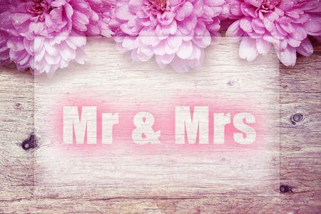 mr and mrs: pink flowers on wooden with word Mr. & Mrs.