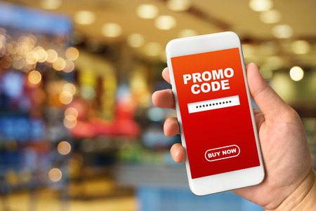 Woman hand holding smartphone against blur bokeh of shop background with word promo code buy now Stockfoto