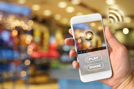 vdo: Woman hand holding smartphone against blur bokeh of shop background VDO ads concept