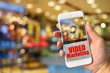 live stream tv: Woman hand holding smartphone against blur bokeh of shop background VIDEO Marketing concept