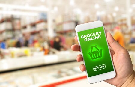 mobile phone screen: Woman hand holding smartphone against blur bokeh of store background Grocery online concept