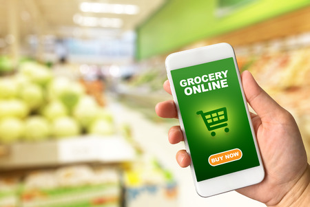 Woman hand holding smartphone against blur bokeh of store background Grocery online concept