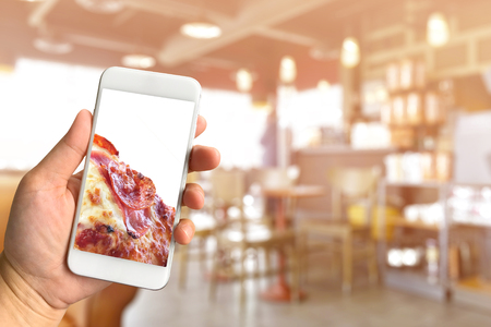 Woman hand holding smartphone pizza with copy space on screen against blurred restaurant background food online concept
