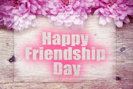 friendship day: pink flowers on wooden with word Happy Friendship Day Stock Photo