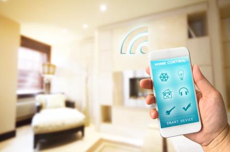Vrouw de hand houden smartphone tegen onscherpte van de woonkamer achtergrond smart home control-concept Stockfoto