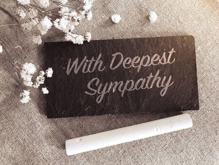 With deepest sympathy note with flowers on small chalk board background