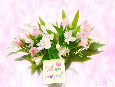 Bouquet of pink and white flowers on pink glitter bokeh background with word will you marry me?
