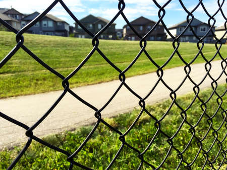 front  or back  yard: chain fence on green grass, houses and sky background
