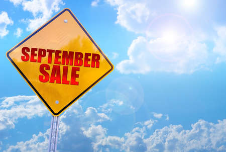 september sale word on yellow traffic sign blue sky background