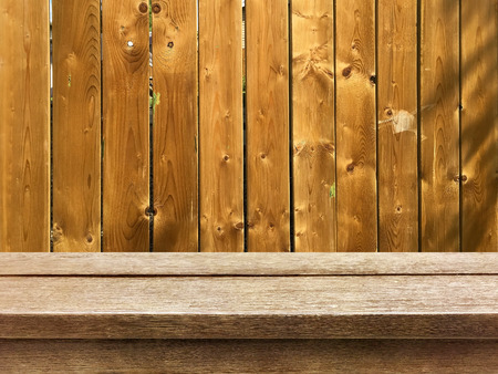 old wood table top on wooden fence background Stock Photo