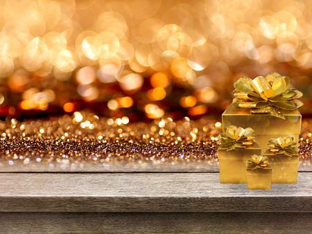 Gold gift boxes and ribbon on wood table, bokeh background Stock Photo