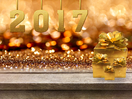 countertop: Gold gift boxes and ribbon with word 2017 on wood table, bokeh background