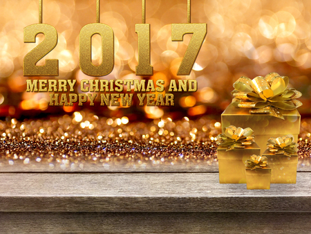 Gold gift boxes and ribbon with word Merry Christmas and Happy new year 2017 on wood table, bokeh background