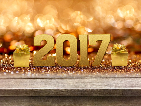 Gold gift box and ribbon with word 2017 on wood table, bokeh background